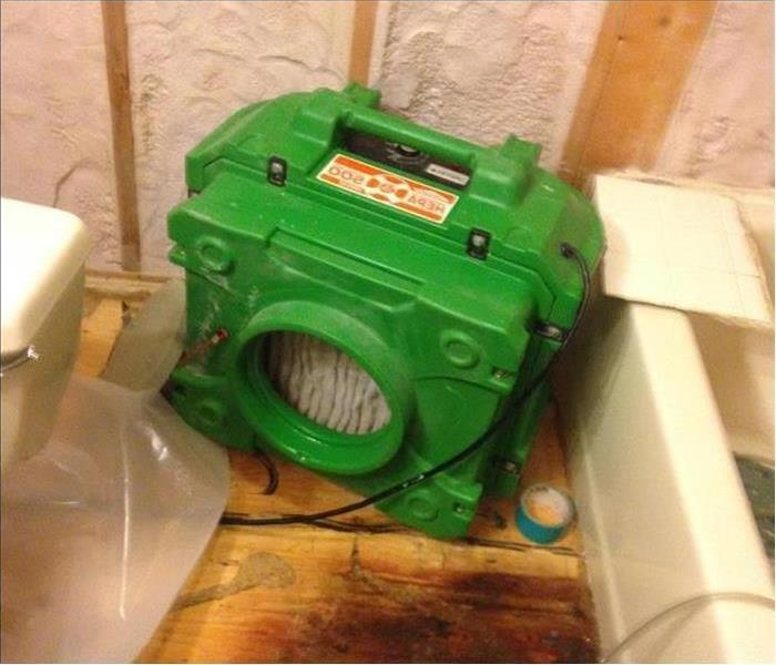 An air scrubber set out in a bathroom removing the odor in the after water damage stuck this home